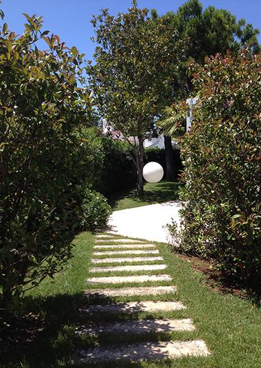 """Studio Talent: il giardino di questa """"villa al mare"""" nel complesso turistico di Rosa Marina a Ostuni, è pensato principalmente per garantire la privacy di chi vive. I gelsomini avvolgono le pareti di un pergolato, alti cespugli ne perimetrano i confini e dei camminamenti pietra nel prato definiscono i percorsi."""