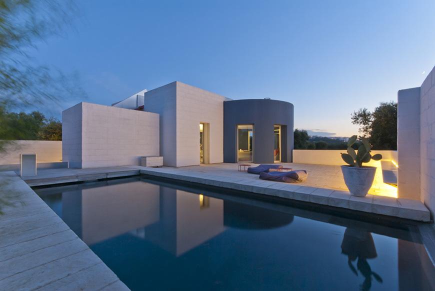 Studio Talent: Uno specchio d'acqua riflette l'architettura di una residenza in campagna.