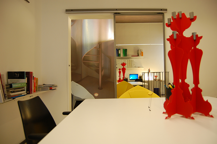 Un appartamento degli anni '70 diviene la sede dello Studio Talent; grandi stampe di alcune realizzazioni dello studio tappezzano le pareti e i soffitti.